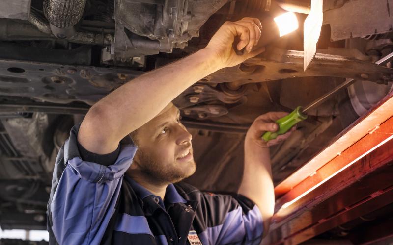 De automonteur kijkt onder de auto met een zaklamp