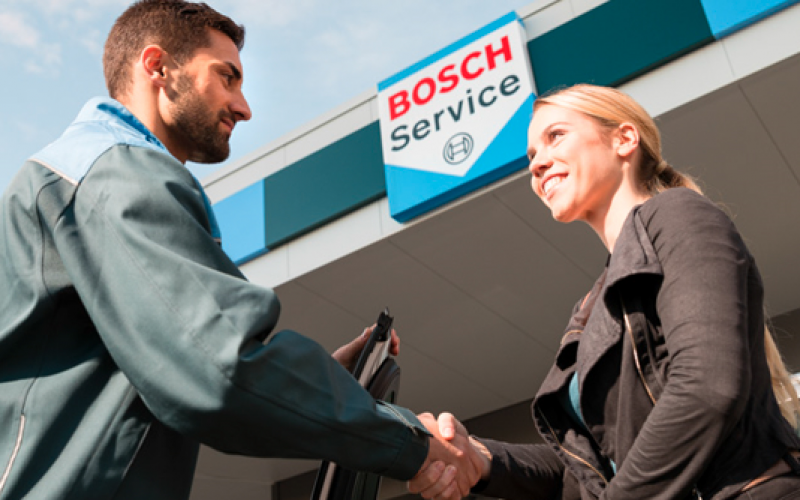 Bosch Car Service monteur schudt de hand met een klant