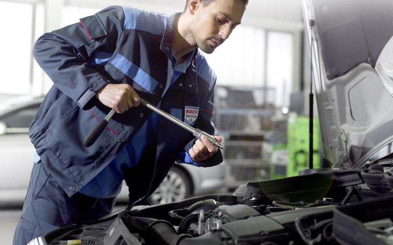 Bosch Car Service monteur monteert een bougie