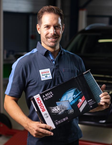 Un mécanicien Bosch Car Service avec un filtre Bosch+ dans ses mains