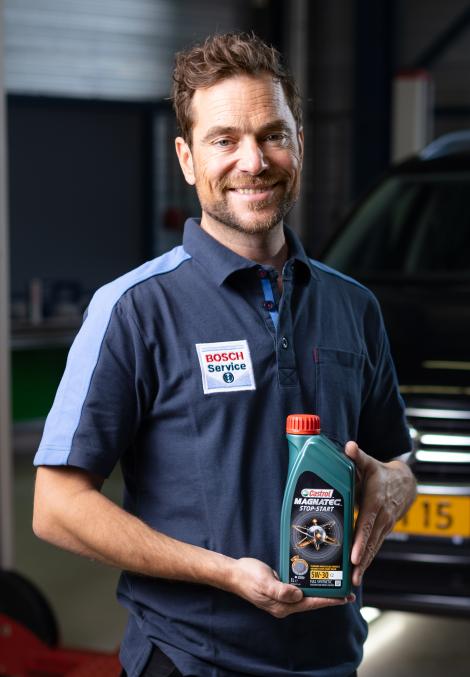 Le mécanicien Bosch Car Service détient une bouteille d'huile moteur de Castrol